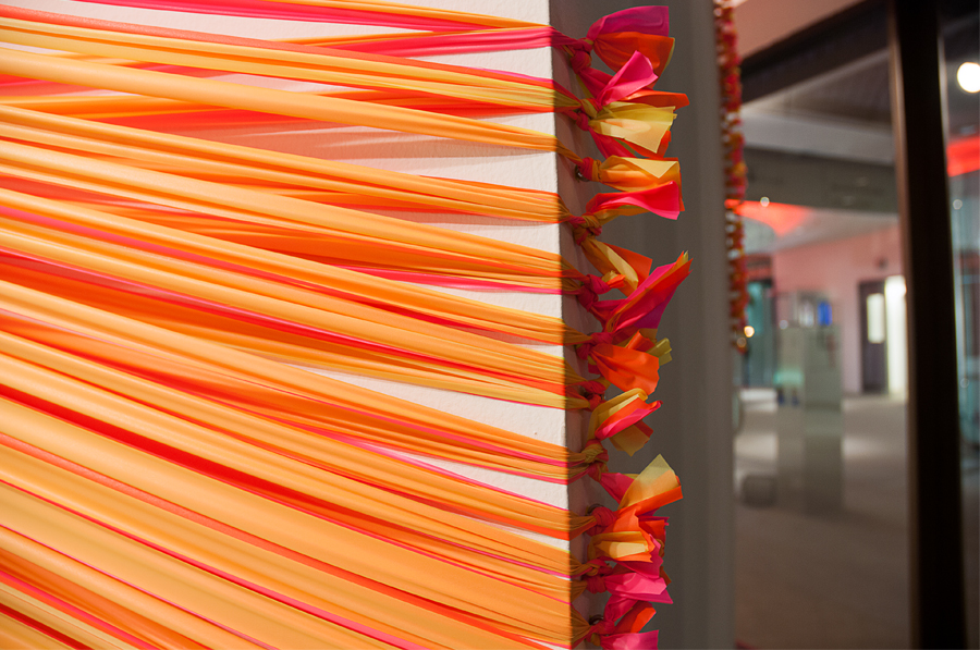 A detail image of florescent pink and yellow strands of flagging tape stretching around the rear corners of an architectural column, terminating in a series of eye hooks.