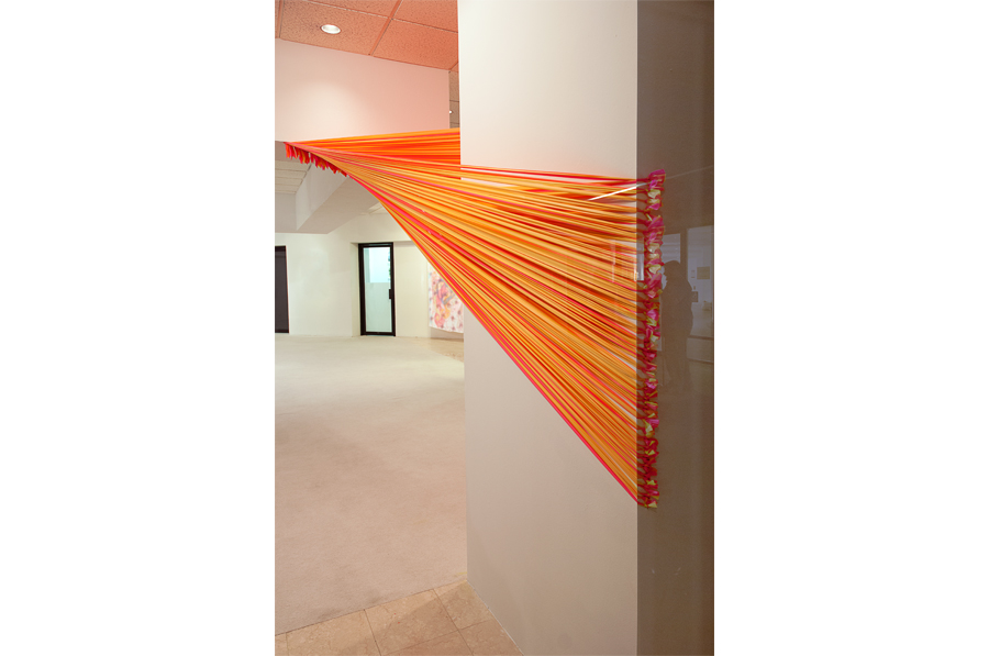 Florescent pink and yellow strands of flagging tape stretch from a plane in the ceiling to a column where it wraps around the rear corners and terminates in a series of eye hooks.