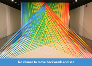 A photo of a site-specific art installation made of linear strands of multi-colored flagging tape arranged in planes that intersect each other in space terminating at a 17 foot long pedestal.