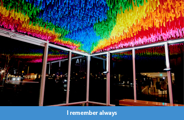 A rainbow-hued, large-scale installation at the Laguna Art Museum in Laguna Beach, California that is suspended from the ceiling, comprised of colorful flagging tape.
