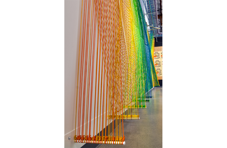 A detail image of a rainbow-hued installation, taken from the side, looking toward the center of the artwork, showing the custom-fabricated, powder-coated hardware that the cords are knotted to.