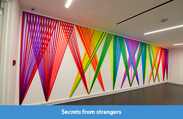 A rainbow hued wall weaving of plastic flagging tape on view at the Wells Fargo Center in Los Angeles, CA