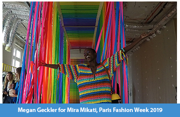 A photograph of a model at the end of an upside down rainbow catwalk designed by Megan Geckler, clothes by Mira Mikati for Paris Fashion Week 2019